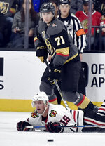 Chicago Blackhawks center Jonathan Toews (19) falls to the ice as Vegas Golden Knights center William Karlsson skates next to him during the second period of an NHL hockey game Tuesday, Feb. 13, 2018, in Las Vegas. (AP Photo/David Becker)