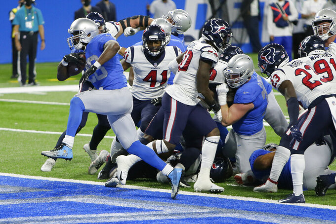 Detroit Lions running back Adrian Peterson breaks through the Houston Texans defense for a 1-yard touchdown run during the first half of an NFL football game, Thursday, Nov. 26, 2020, in Detroit. (AP Photo/Duane Burleson)