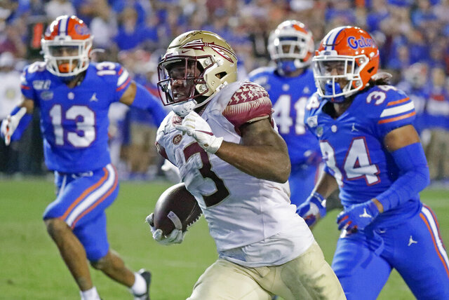 Florida State running back Cam Akers (3) runs for a 50-yard touchdown past Florida linebacker Lacedrick Brunson (34) and defensive back Donovan Stiner (13) during the second half of an NCAA college football game Saturday, Nov. 30, 2019, in Gainesville, Fla. (AP Photo/John Raoux)