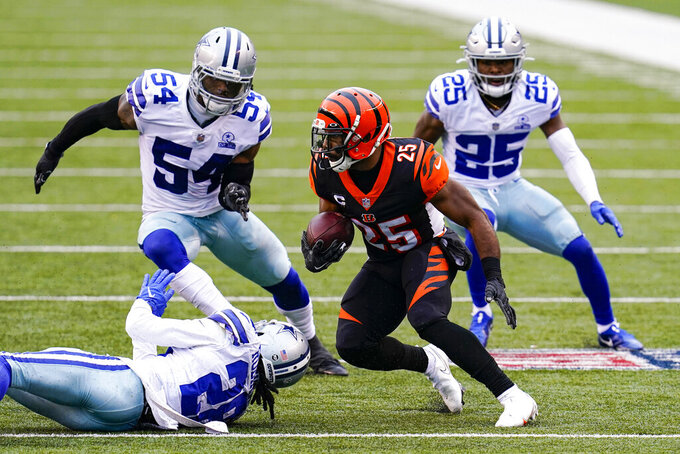 Cincinnati Bengals running back Giovani Bernard (25) is pursued after a catch by Dallas Cowboys middle linebacker Jaylon Smith (54) and free safety Xavier Woods (25) in the second half of an NFL football game in Cincinnati, Sunday, Dec. 13, 2020. (AP Photo/Bryan Woolston)
