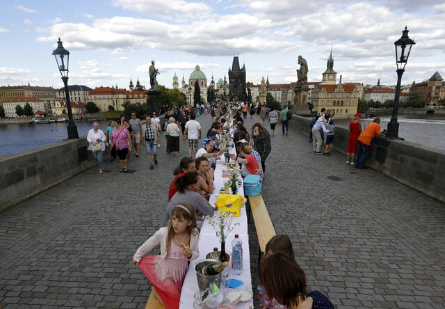 FILE - In this Tuesday, June 30, 2020 file photo, residents sit to dine on a 500 meter long table set on the medieval Charles Bridge, after restrictions were eased following the coronavirus pandemic in Prague, Czech Republic. Weeks after the citizens of Prague said a symbolic farewell to the coronavirus, the second wave has struck hard and the number of confirmed cases is setting new records almost daily. It is currently at a similar level to its neighbor German, which has a population eight times the size. The health minister has announced new restrictions, including closing bars, restaurants and clubs at midnight and making it mandatory to wear masks in all spaces in schools. (AP Photo/Petr David Josek, File)