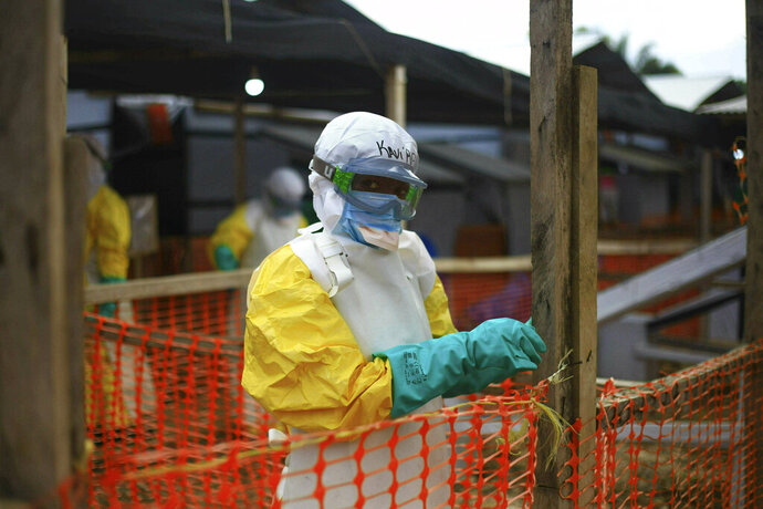 FILE - In this Tuesday April, 16, 2019 file photo, an Ebola health worker is seen at a treatment center in Beni, Eastern Congo. Internal documents by The Associated Press show the World Health Organization spent nearly $192 million on travel last year, with staffers sometimes breaking the rules by flying in business class, booking expensive last-minute tickets and traveling without the required approvals. (AP Photo/Al-hadji Kudra Maliro, file)