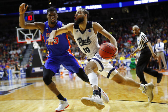 Nevada forward Caleb Martin drives past Florida center Kevarrius Hayes, left, during a first round men's college basketball game in the NCAA Tournament, Thursday, March 21, 2019, in Des Moines, Iowa. (AP Photo/Charlie Neibergall)
