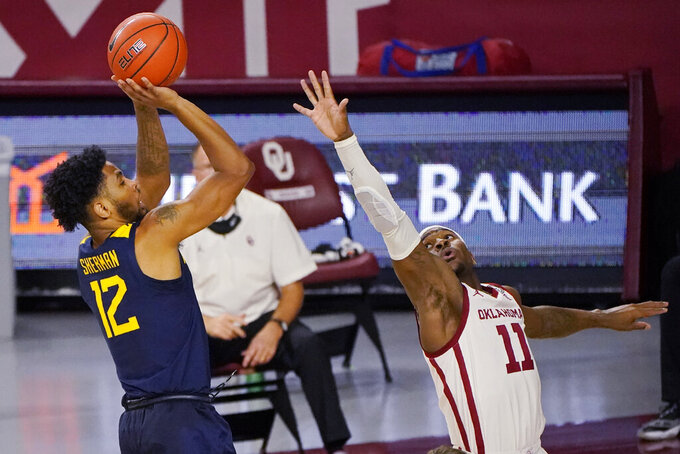 West Virginia guard Taz Sherman (12) shoots over Oklahoma guard De'Vion Harmon (11) in the first half of an NCAA college basketball game Saturday, Jan. 2, 2021, in Norman, Okla. (AP Photo/Sue Ogrocki)