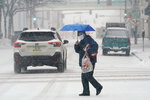 A pedestrian crosses a snow covered street, Monday, Jan. 25, 2021, in downtown Des Moines, Iowa. A major winter storm is expected to blanket a large swath of the middle of the country with snow Monday and disrupt travel as more than a foot of snow falls in some areas. (AP Photo/Charlie Neibergall)
