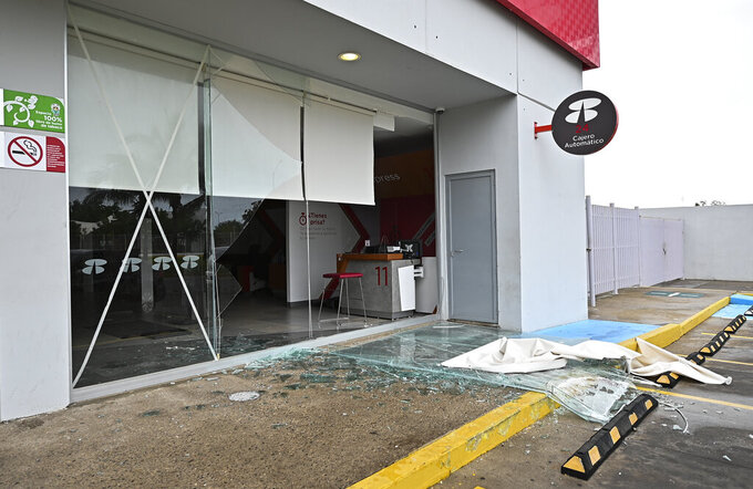 Shattered glass covers the entrance of a bank after the passing of Hurricane Pamela in Mazatlan, Mexico, Wednesday, Oct. 13, 2021. Pamela made landfall on Mexico's Pacific coast just north of Mazatlan on Wednesday, bringing high winds and rain to the port city. (AP Photo/Roberto Echeagaray)