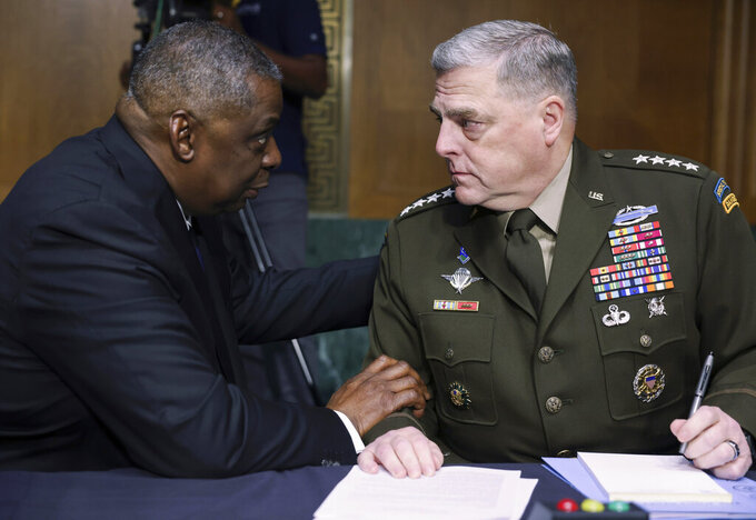 Secretary of Defense Lloyd Austin, left, and Chairman of the Joint Chiefs Chairman Gen. Mark Milley talk before a Senate Appropriations Committee hearing to examine proposed budget estimates and justification for fiscal year 2022 for the Department of Defense in Washington on Thursday, June 17, 2021. (Evelyn Hockstein/Pool via AP)