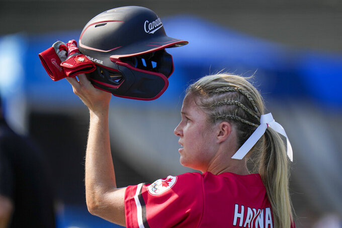 FILE - In this July 21, 2021 file photo, Canada's Victoria Hayward holds her helmet aloft during the softball game between Mexico and Canada at the 2020 Summer Olympics in Fukushima , Japan.  Hayward will be back on the field this weekend as a softball player — and as an owner. After hitting .300 at the Tokyo Olympics, the Canadian outfielder heads one of four teams that start play Saturday, Aug. 28,  at Athletes Unlimited outside Chicago.(AP Photo/Jae C. Hong, File)