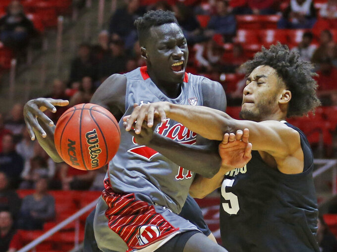 Colorado guard D'Shawn Schwartz (5) defends against Utah forward Both Gach (11) as he goes to the basket during the second half in an NCAA college basketball game Sunday, Jan. 20, 2019, in Salt lake City. (AP Photo/Rick Bowmer)