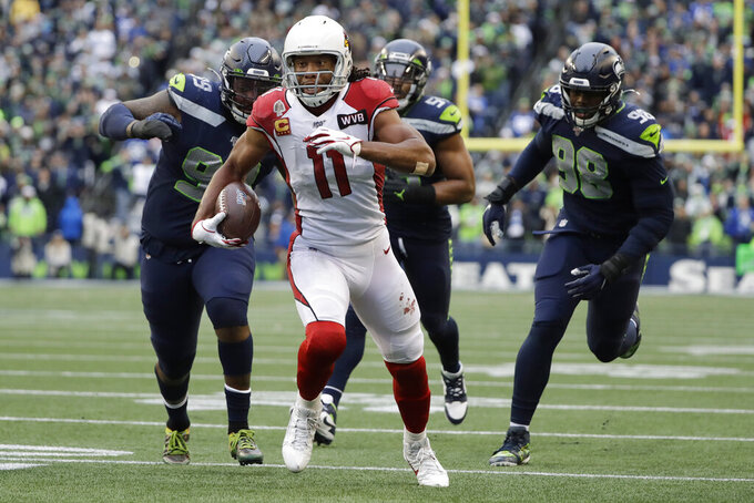 Arizona Cardinals wide receiver Larry Fitzgerald (11) runs for a touchdown after a reception as Seattle Seahawks defensive tackle Quinton Jefferson, left, and defensive end Rasheem Green, right, pursue during the first half of an NFL football game, Sunday, Dec. 22, 2019, in Seattle. (AP Photo/Elaine Thompson)