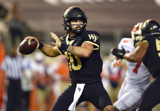 FILE - Wake Forest quarterback Sam Hartman drops back to throw during an NCAA college football game against Clemson in Winston-Salem, N.C., in this Saturday, Sept. 12, 2020, file photo. The Demon Deacons return nine starters on both offense and defense. (Walt Unks/The Winston-Salem Journal via AP, File)
