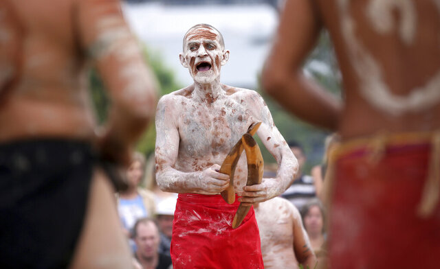 FILE - In this Jan. 26, 2017, file photo a member of the Aboriginal community takes part in a traditional smoking ceremony that is performed as part of Australia Day celebration in Sydney. Cricket Australia has run afoul of the country's prime minister for refusing to refer to the national holiday in the marketing of three matches on Jan. 26 after a recommendation from its Indigenous advisory committee. (AP Photo/Rick Rycroft, File)