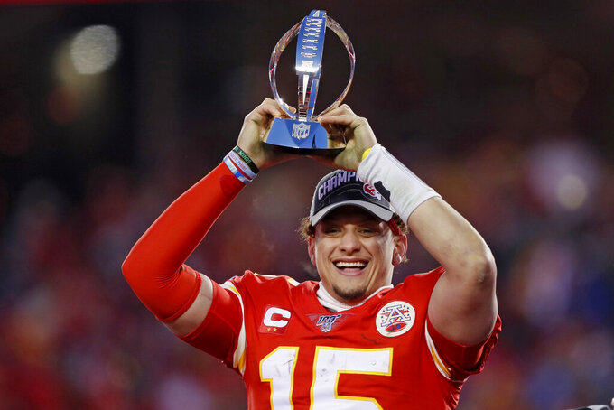 Kansas City Chiefs' Patrick Mahomes celebrates with the Lamar Hunt Trophy after the NFL AFC Championship football game against the Tennessee Titans Sunday, Jan. 19, 2020, in Kansas City, MO. The Chiefs won 35-24 to advance to Super Bowl 54. (AP Photo/Charlie Neibergall)