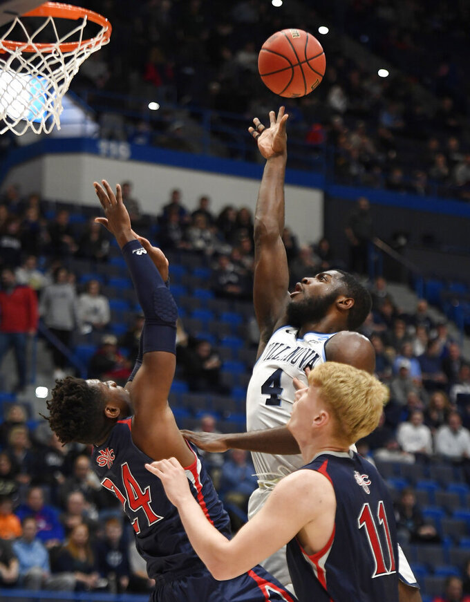 Villanova's Eric Paschall (4) shoots as St. Mary's Malik Fitts (24) and Matthias Tass (11) defend during the first half of a first round men's college basketball game in the NCAA tournament, Thursday, March 21, 2019, in Hartford, Conn. (AP Photo/Jessica Hill)