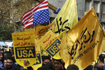 Demonstrators hold anti-U.S. banners and a torn makeshift U.S. flag upside down in an annual rally in front of the former U.S. Embassy in Tehran, Iran, Monday, Nov. 4, 2019. Reviving decades-old cries of