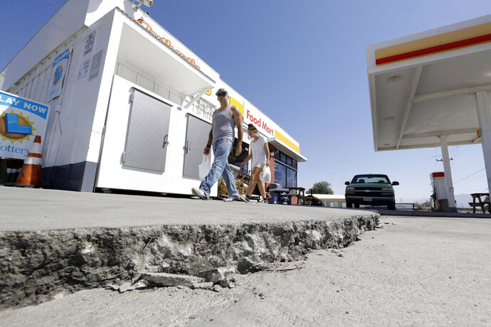 FILE - This July 6, 2019 photo shows crack in a gas station's driveway in the aftermath of an earthquake in Trona, Calif. Officials say Thursday, July 11, 2019, that two Southern California desert communities, Ridgecrest and Trona, struck by last week's powerful earthquakes may have sustained as little damage as they did because they have no tall buildings and many homes are fairly new and built to strict earthquake standards. Nearby Trona, with a population of about 2,000, was harder hit, and commissioners noted many of its buildings are older. (AP Photo/Marcio Jose Sanchez, File)