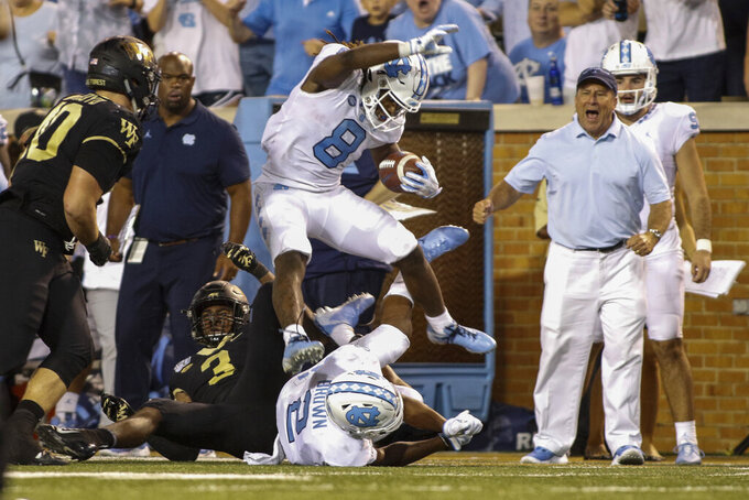 North Carolina running back Michael Carter (8) leaps over Wake Forest defensive back Nasir Greer (3) and North Carolina wide receiver Dyami Brown (2) during the second half of an NCAA college football game in Winston-Salem, N.C., Friday, Sept. 13, 2019. Wake Forest won 24-18. (AP Photo/Nell Redmond)