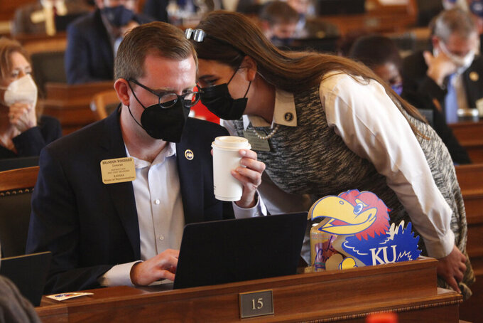 Kansas state Reps. Brandon Woodard, left, D-Lenexa, and Stephanie Clayton, right, D-Overland Park, confer during a House debate on a bill aimed at ensuring that all public school districts offer all students full-time, in-person classes, Monday, March 22, 2021, at the Statehouse in Topeka, Kan. The bill sets a March 31, 2021, deadline, and Democrats argue that such decisions should be left to local boards of education. (AP Photo/John Hanna)