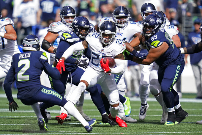 Tennessee Titans running back Derrick Henry (22) rushes as Seattle Seahawks defensive end Alton Robinson (98) and defensive tackle Al Woods (99) close in during the first half of an NFL football game, Sunday, Sept. 19, 2021, in Seattle. (AP Photo/Elaine Thompson)