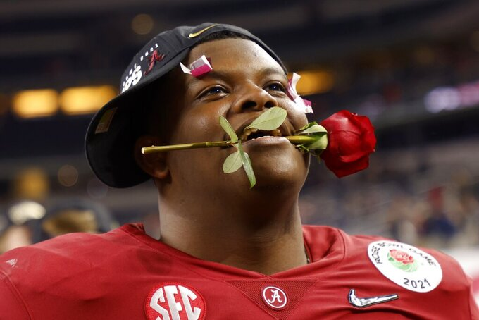Alabama offensive lineman Javion Cohen holds a rose between his teeth after their 31-14 win against Notre Dame in the Rose Bowl NCAA college football game in Arlington, Texas, Friday, Jan. 1, 2021. (AP Photo/Michael Ainsworth)