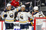 Buffalo Sabres center Sam Reinhart (23) celebrates his goal with Jack Eichel (9) and Jeff Skinner (53) in the third period of an NHL hockey game against the Detroit Red Wings, Friday, Oct. 25, 2019, in Detroit. (AP Photo/Paul Sancya)