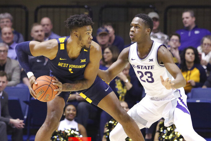 West Virginia forward Derek Culver (1) goes to pass the ball as he is defended by Kansas State forward Montavious Murphy (23) during the first half of an NCAA college basketball game Saturday, Feb. 1, 2020, in Morgantown, W.Va. (AP Photo/Kathleen Batten)