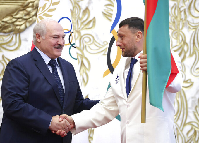 FILE In this file photo taken on Friday, July 9, 2021, Belarus President Alexander Lukashenko, left, presents the national flag to the captain of Belarus National Olympic team Ivan Tikhon ahead of the Summer Olympics Games in Tokyo, Minsk, Belarus. Lukashenko, who has a keen interest in sports and served as the head of the Belarus National Olympic Committee for nearly a quarter-century before handing over the post to his older son in February, has sternly warned the country's Olympic athletes that they better show high performance. (Maxim Guchek/BelTA Pool Photo via AP, File)
