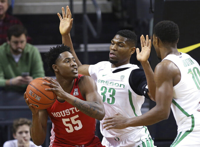 Houston's Brison Gresham, left, looks for a teammate under pressure from Oregon's Francis Okoro, center, and Shakur Juiston during the first half of an NCAA college basketball game in Eugene, Ore., Friday, Nov. 22, 2019. (AP Photo/Chris Pietsch)