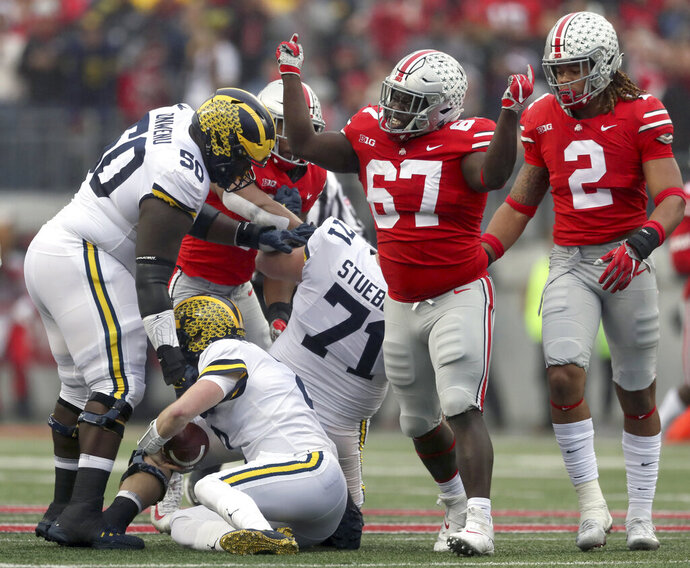 In this Saturday, Nov. 24, 2018, photo, Ohio State defensive lineman Robert Landers (67) celebrates his sack on Michigan quarterback Shea Patterson (2) in the first half of an NCAA college football game in Columbus, Ohio. Robert Landers struggles with mental illness, and he doesn't care who knows it. In fact, he wants more people to know it. He took to Twitter in the aftermath of the mass shooting in his hometown of Dayton to make his struggle public, understanding that survivors of the shooting and others may have issues to contend with. (Marvin Fong/The Plain Dealer via AP)