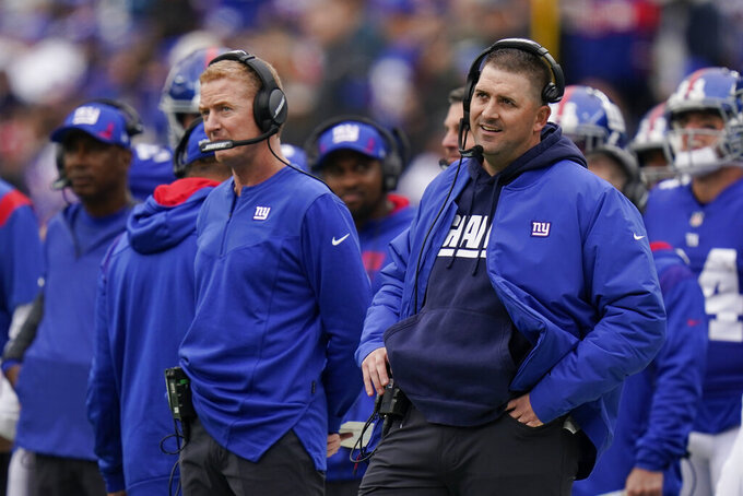 New York Giants head coach Joe Judge, right, and offensive coordinator Jason Garrett, left, react during the first half of an NFL football game against the Carolina Panthers, Sunday, Oct. 24, 2021, in East Rutherford, N.J. (AP Photo/Seth Wenig)