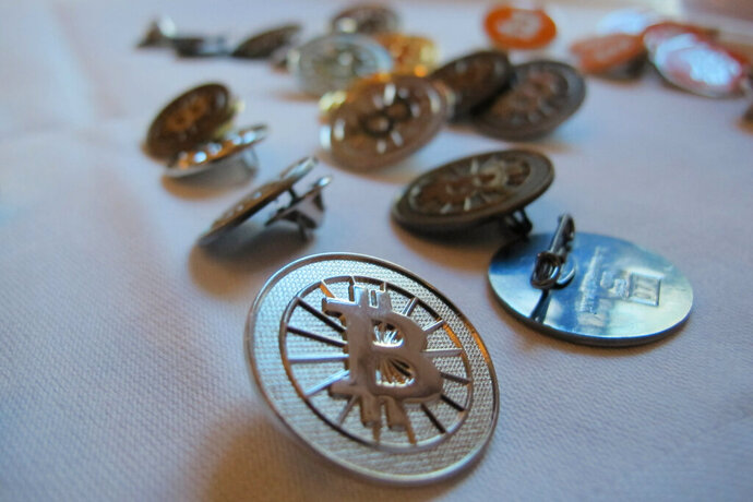 FILE-In this Feb. 12, 2014 file photo Bitcoin buttons are displayed on a table at the Inside Bitcoins conference in Berlin. Researchers calculate that the electricity required for the virtual currency bitcoin generates as much carbon dioxide as cities like Las Vegas or Hamburg. (AP Photo/Frank Jordans)