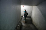 Dr. Jeanie Tse, chief medical officer at the Institute for Community Living, walks down a stairwell towards the exit of the a public housing complex after administering antipsychotic medication to a patient living with schizophrenia, Wednesday, May 6, 2020, in the Brooklyn borough of New York. (AP Photo/John Minchillo)