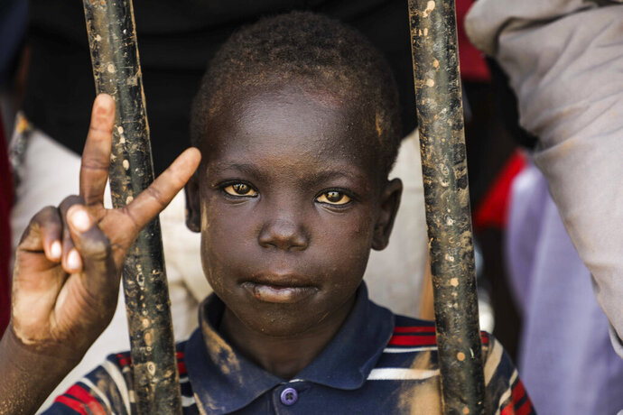 Sudanese boy flashes victory sign during a protest condemning a deadly crackdown last month in Khartoum, Sudan, Thursday, July 18, 2019. Thousands of Sudanese have joined protests as tensions remain high despite recent progress toward a power-sharing deal with the ruling military council. (AP Photo/Mahmoud Hjaj)