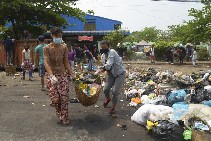 """Anti-coup protesters use garbage to block a road as a form of """"silent protest"""" in Yangon, Myanmar on Tuesday, March 30, 2021. At least 510 protesters have been killed since the coup, as of Tuesday, according to Myanmar's Assistance Association for Political Prisoners, which says the actual toll is likely much higher. (AP Photo)"""