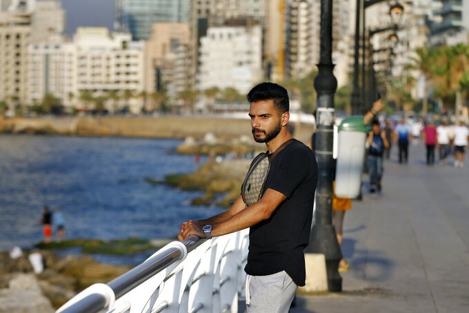 Lebanese Ali Mallah, 27, who recently lost his job as a salesman at a shoe store in Beirut, stands on Beirut's waterfront promenade on the Mediterranean Sea in Beirut, Lebanon, Wednesday, July 22, 2020. Millions of youth in the Middle East region have had job prospects, plans for higher education and marriage upended by the pandemic. While such turmoil and uncertainty is universal in the wake of the coronavirus, the despair is particularly pronounced in Arab countries, where wave after wave of war, displacement and corruption has left this generation feeling bitter and hopeless. (AP Photo/Bilal Hussein)