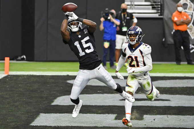 Las Vegas Raiders wide receiver Nelson Agholor (15) misses a catch in the endzone against Denver Broncos cornerback A.J. Bouye (21) during the first half of an NFL football game, Sunday, Nov. 15, 2020, in Las Vegas. (AP Photo/David Becker)