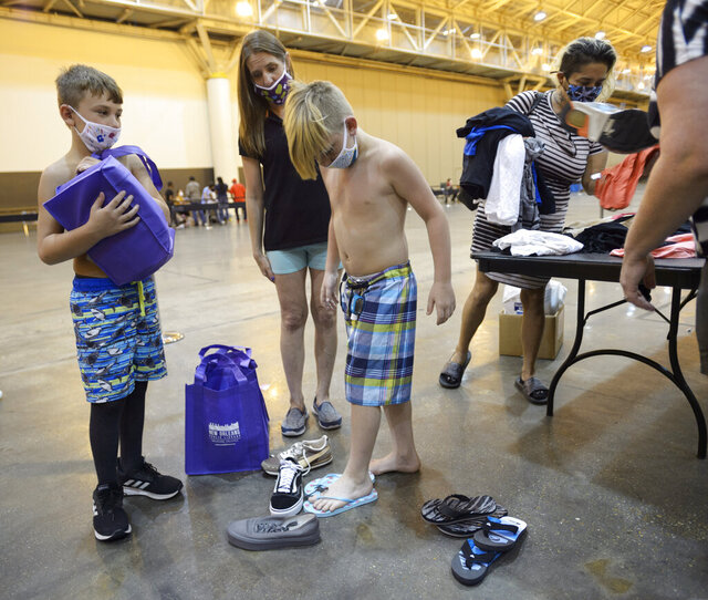 Evacuees from Hurricane Laura Bentley White, 9, center, tries on shoes with Chris Cormier, 10, left, and Angela Cormier while visiting an aid center at the Ernest N. Morial Convention set up by the Federal Emergency Management Agency and Governor's Office of Homeland Security & Emergency Management in New Orleans, La. Monday, Aug. 31, 2020. (Max Becherer/The Advocate via AP)