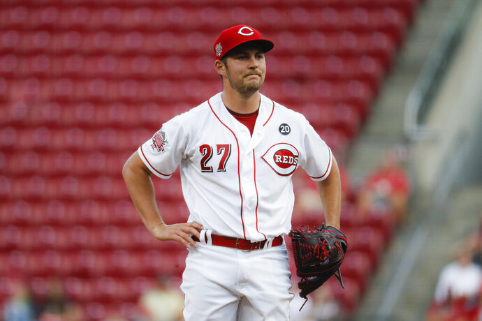 """FILE - In this Aug. 19, 2019 file photo Cincinnati Reds starting pitcher Trevor Bauer reacts after walking San Diego Padres' Josh Naylor in the first inning of a baseball game in Cincinnati. Bauer sent a series of tweets during the weekend, starting with a jab about Major League Baseball's threat to cut ties with minor league affiliates. Bauer followed up with: """"At least Rob Manfred is trying to ruin baseball at all levels and isn't discriminating."""" MLB had no immediate comment to Bauer's remarks, Sunday, Dec. 15, 2019. Manfred recently said MLB was pushing ahead with a rules change for 2020 that requires pitchers to face at least three batters or finish a half-inning. (AP Photo/John Minchillo)"""