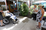 Sisters Elaine Krohn and Lori Hall, far right, wave to their mother Eva Davis, 94, outdoors at the Hebrew Rehabilitation Center, Wednesday June 10, 2020, in Boston, under the state's new nursing home visitation guidelines which requires social distancing. The women hadn't been able to visit in person since March. (AP Photo/Elise Amendola)