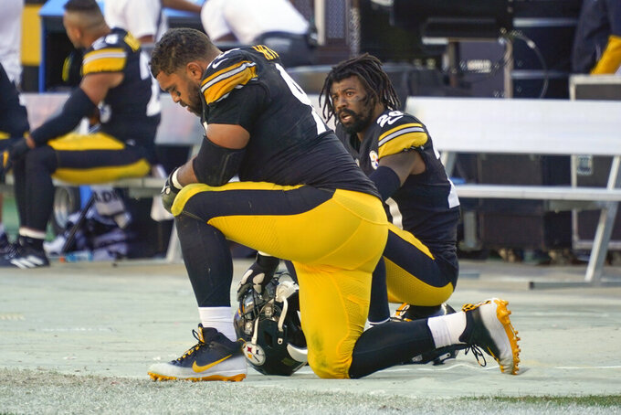 Pittsburgh Steelers defensive end Cameron Heyward, left, kneels on the sideline as his team is losing against the Cincinnati Bengals during the second half an NFL football game, Sunday, Sept. 26, 2021, in Pittsburgh. The Bengals won 24-10. (AP Photo/Gene J. Puskar)