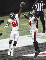 Tampa Bay Buccaneers wide receiver Antonio Brown, left, celebrates his winning touchdown with Chris Godwin for a victory over the Atlanta Falcons in the final minutes of an NFL football game Sunday, Dec. 20, 2020, in Atlanta. (Curtis Compton/Atlanta Journal-Constitution via AP)