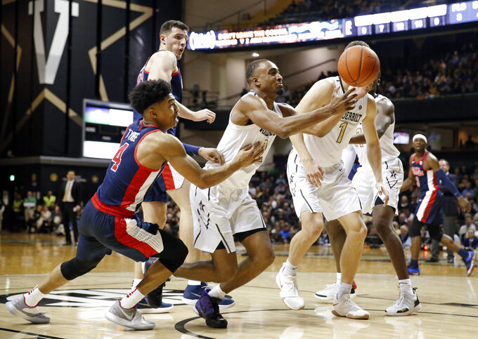 Vanderbilt guard Joe Toye, center, reaches for the ball in front of Mississippi guard Breein Tyree (4) in the second half of an NCAA college basketball game Saturday, Jan. 5, 2019, in Nashville, Tenn. (AP Photo/Mark Humphrey)