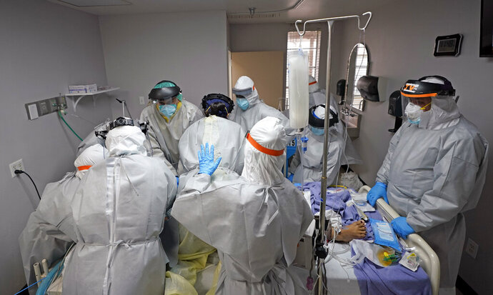 Dr. Joseph Varon, right, leads a team as they try to save the life of a patient unsuccessfully inside the Coronavirus Unit at United Memorial Medical Center, Monday, July 6, 2020, in Houston. Hospitalizations due to COVID-19 in the second-largest state in the U.S. have more than doubled in the last two weeks. (AP Photo/David J. Phillip)