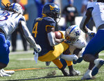 West Virginia running back Leddie Brown (4) is tackled by Kansas safety Davon Ferguson (7) during an NCAA college football game, Saturday, Oct. 17, 2020, in Morgantown, W.Va. (William Wotring/The Dominion-Post via AP)