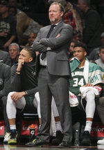 Milwaukee Bucks forward Giannis Antetokounmpo, right, sits with foul trouble early as head coach Mike Budenholzer, center, monitor action, during a NBA basketball game against the Brooklyn Nets, Saturday, Jan. 18, 2020, in New York. (AP Photo/Bebeto Matthews)