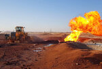 In this photo released by the Syrian official news agency SANA, Syrian firefighters use a bulldozer to extinguish the flames of a gas pipeline that hit by an explosion, between the northeastern Damascus suburbs of Adra and Dumair, in Syria Monday, Aug. 24, 2020. An explosion early on Monday struck a gas pipeline in a Damascus suburb, cutting electricity throughout Syria, state media reported, citing the country's electricity and oil ministers. (SANA via AP)