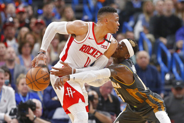 Oklahoma City Thunder guard Dennis Schroeder (17) knocks the ball away from Houston Rockets guard Russell Westbrook (0) during the first half of an NBA basketball game Thursday, Jan. 9, 2020, in Oklahoma City. (AP Photo/Sue Ogrocki)