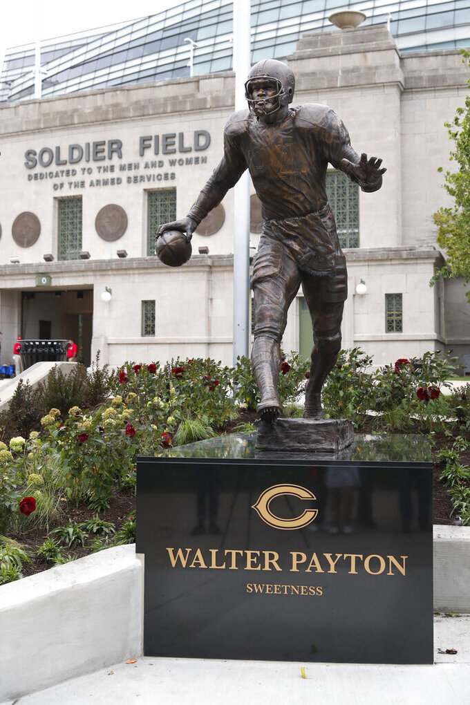 The newly dedicated statue of Chicago Bears and Pro Football Hall of Fame running back Walter Payton stands outside Soldier Field during a unveiling ceremony of statues honoring George Halas and Payton, Tuesday, Sept. 3, 2019, in Chicago. (AP Photo/Charles Rex Arbogast)