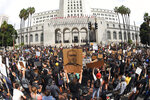 In this photo taken with a wide angle lens, demonstrators stand in front of Los Angeles City Hall during a protest over the death of George Floyd Tuesday, June 2, 2020, in Los Angeles. Floyd died in police custody on Memorial Day in Minneapolis. (AP Photo/Mark J. Terrill)