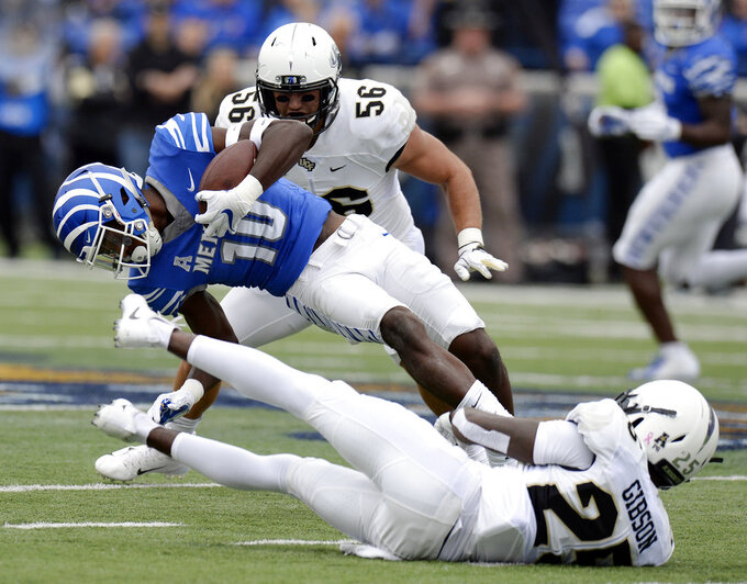 Memphis wide receiver Damonte Coxie (10) is brought down by Central Florida defensive back Kyle Gibson (25) after catching a pass during the first half of an NCAA college football game Saturday, Oct. 13, 2018, in Memphis, Tenn. (AP Photo/Mark Zaleski)
